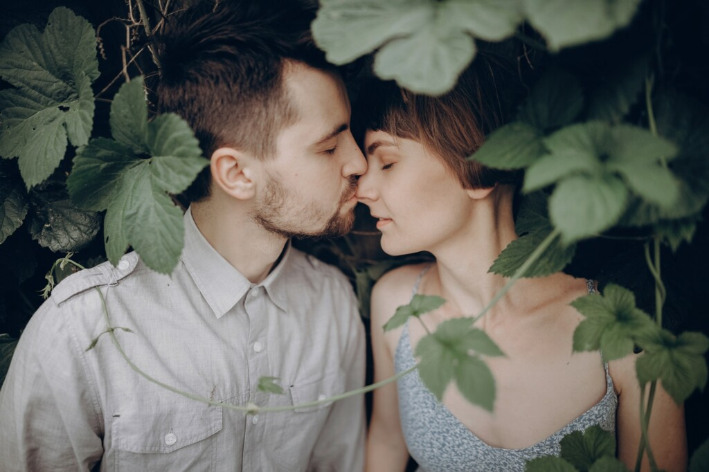 stylish-hipster-couple-kissing-in-green-leaves-holding-hands.jpg